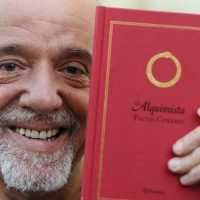 Brazilian writer Paulo Coelho holds up a copy of his novel The Alchemist, which has sold more than 100 million copies, while attending a news conference in Aviles, northern Spain, May 29, 2008. Coelho will attend a homage and an exhibition to celebrate the 20th anniversary of the publication of the book.  REUTERS/Eloy Alonso (SPAIN)